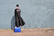 Mime in black cape standing on plastic box in front of blue wall.
