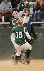 30 March 2013:  Katie Crane pulls in a popped up ball in front of Chloe Montgomery during an NCAA Division III women's softball game between the DePauw Tigers and the Illinois Wesleyan Titans in Bloomington IL<br />