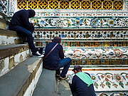 "11 SEPTEMBER 2017 - BANGKOK, THAILAND: Workers finishing up the renovation of Wat Arun. Renovations are nearly finished at Wat Arun on the Thonburi side of the Chao Phraya River in Bangkok. Wat Arun is famous for its Khmer style main ""prang"" (chedi). It was originally built in the Ayutthaya Period and rebuilt to its current form in the time of Rama II.      PHOTO BY JACK KURTZ"