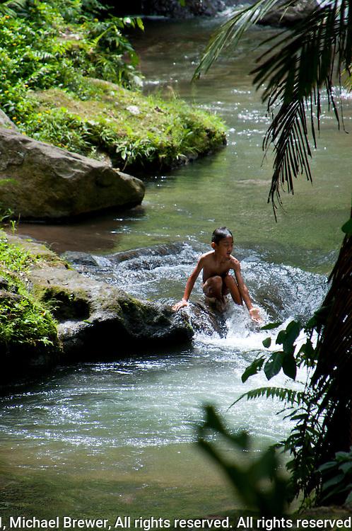 Boy playing in a river near Ubud, Bali, Indonesia
