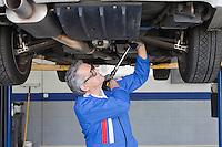 Car mechanics working below a car using a monkey wrench