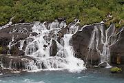 Waterfalls flowing down the rock. Hraunfossar. Iceland.