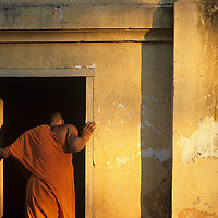 Asia, Laos, Luang Prabang, Young Buddhist monks outside Wat Nong Sikhunmeuang Temple at sunset
