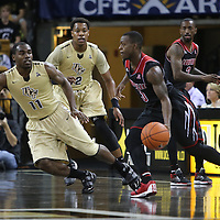 Louisville Cardinals guard Chris Jones (3) drives the ball against UCF Knights guard Calvin Newell (11) during an NCAA basketball game between the 14th ranked Louisville Cardinals and the UCF Knights at the CFE Arena on Tuesday, December 31, 2013 in Orlando, Florida. (AP Photo/Alex Menendez)