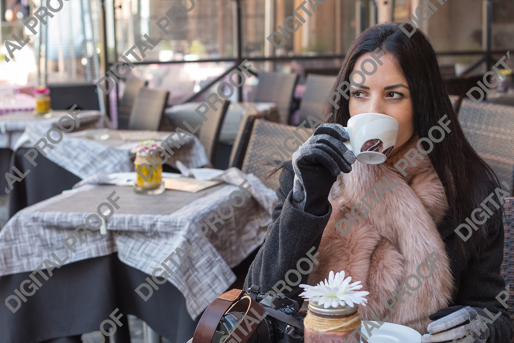 Thinking and positive Woman drinking coffee in the morning and sitting in street cafe in Rome Italy.