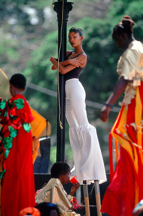 ".Trinidad and Tobago ""MOKO JUMBIES: The Dancing Spirits of Trinidad"".(Adanna de Souza, Dragon's daughter, holds onto a pole at Woodford   Square in Port of Spain awaiting the start of a parade).A photo essay about a stilt walking school in Cocorite, Trinidad..Dragon Glen de Souza founded the Keylemanjahro School of Art & Culture in 1986. The main purpose of the school is to keep children off the streets and away from drugs..He first taught dances like the Calypso, African dance and the jig with his former partner Cathy Ann Samuel.  Searching for other activities to engage the children in, he rediscovered the art of stilt-walking, a tradition known in West Africa as the Moko Jumbies , protectors of the villages and participants in religious ceremonies. The art was brought to Trinidad by the slave trade and soon forgotten..Today Dragon's school has over 100 members from age 4 and up..His 2 year old son Mutawakkil is probably the youngest Moko Jumbie ever. The stilts are made by Dragon and his students and can be as high as 12-15 feet. The children show their artistic talents mostly at the annual Carnival, which today is unthinkable without the presence of the Moko Jumbies. A band can have up to 80 children on stilts and they have won many of the prestigious prizes and trophies that are awarded by the National Carnival Commission. Designers like  Peter Minshall , Brian Mac Farlane and Laura Anderson Barbata create dazzling costumes for the school which are admired by thousands of  spectators. Besides stilt-walking the children learn the limbo dance, drumming, fire blowing and how to ride  unicycles..The school is situated in Cocorite, a suburb of Port of Spain, the capital of Trinidad and Tobago..all images © Stefan Falke"
