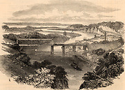 South Wales Railway: Opening of the Chepstow Bridge, 1852. Wrought iron tubular suspension bridge over the river Wye at Chepstow.  This bridge, constructed 1849-1852, was an innovative design by Sambaed Kingdom Brunel (1806-1859) and the use of wrought iron tubular girders is considered to be a dummy run for his last great masterpiece, the Royal Albert bridge over the Tamar at Saltash.   The Chepstow bridge carried the South Wales Railway over the Wye just above its junction with the Severn. Brunel was engineer to the railway.   From 'The Illustrated London News'. (London, 24 July 1852).