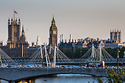 A view of the Houses of Parliament over the River Thames, London, United Kingdom.  The Houses of Parliament includes the House of Commons and the House of Lords which forms the British Government.  The famous Big Ben bell tower is an iconic part of the Houses of Parliament. Traffic drives past on Waterloo bridge including a double decker red bus.