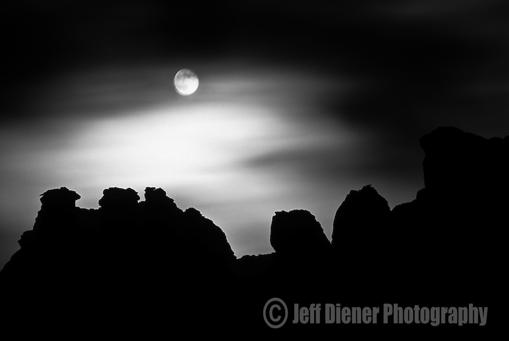 A rising moon illuminates clouds and creates hoodoo silhouettes in Canyonlands National Park, Utah.