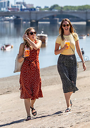 © Licensed to London News Pictures. 07/08/2020. London, UK. Two young women enjoy a cooling beer in the sunshine next to the River Thames at Putney  Embankment in South West London as temperatures are expected to reach to 35c today. Thousands of sunseekers have flocked to parks, rivers and the south coast as temperatures soar with beaches and roads becoming jammed with holidaymakers. The heat is set to continue for the rest of the week with temperatures expected in the high 20s. Photo credit: Alex Lentati/LNP
