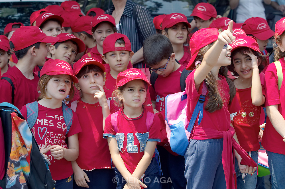 School children watching the clock tower of the dome church. Every noon, guilded figures play Christ's resurrection and other scenes to the sound of the bells and a mechanic organ.
