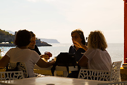 Sorrento, Italy, September 18 2017. Friends enjoy a drink at a seaside restaurant overlooking Capo di Massa and the distant island of Capri near Sorrento, Italy. © Paul Davey