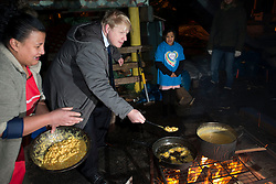 © Licensed to London News Pictures.14/01/2014. London, UK.London Mayor Boris Johnson cooks food at the Glamis Adventure Playground during his visit the Shadwell Community Project in East London in celebration of The Health Lottery's pledge to raise £10 million for local London charities by 2016.Photo credit : Peter Kollanyi/LNP