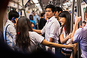 21 JUNE 2013 - BANGKOK, THAILAND: Thai students riding the Silom Line of the Bangkok Skytrain, also called the BTS. The system consists of 32 stations along two lines: the Sukhumvit Line running northwards and eastwards, terminating at Mo Chit and Bearing respectively, and the Silom Line which plies Silom and Sathon Roads, the Central Business District of Bangkok, terminating at the National Stadium and Wongwian Yai. The lines interchange at Siam Station and have a combined route distance of 55 km.       PHOTO BY JACK KURTZ