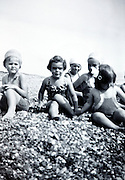 little children playing with shells on the beach early 1950s