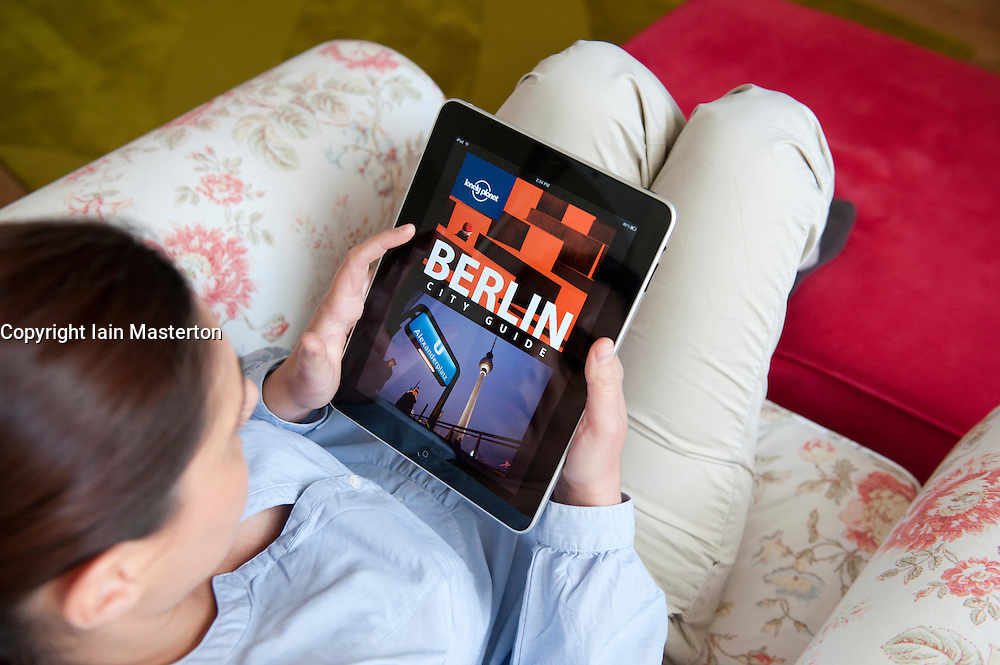 Woman using iPad tablet computer to read ebook travel guidebook to Berlin