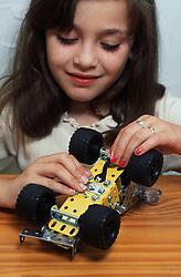 Young girl assembling meccano racing car,