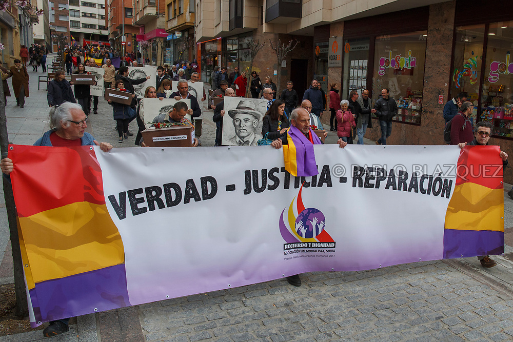 14/04/2018. Relatives and supporters carry a banner reading 'Truth, justice and reconciliation', coffins containing the bodies of victims of Spain Civil War and portraits depicting them along the streets of Soria city during a homage to hand the remains to their families on April 14, 2018 in Soria, Spain. La Asociacion Soriana Recuerdo y Dignidad (ASRD) 'The Soria Association for Memory and Dignity' celebrated a tribute to hand over the remains of civil war victims to their families. The Society of Sciences of ARANZADI helped with the research, exhumation and identification of the bodies, after villagers passed the information about the mass grave, 81 years after the assassination took place, to the ASRD. Seven people were assassinated around August 25, 1936 by Falangists, as part of General Francisco Franco armed forces, and buried in the 'Fosa de los Maestros' (Teachers Mass Grave) near Cobertelada, Soria, after being taken from prison of Almazan during the Spanish Civil War. Five of them were teachers in the region, and also friends of Spanish writer Antonio Machado. The other two still remain unidentified. Another body was assassinated by Falangists accompanied by a priest in 1936, and was exhumed on 23 September of 2017 near Calata&ntilde;azor, Soria. It belonged to Abundio Andaluz, a politician, lawyer and musician in Soria.<br /> Spain's Civil War took the lives of thousands of people on both sides, and civilians. But Franco continued his executions after the war has finished. Teachers, as part of the education sector, were often a target of Franco's forces. Spanish governments has never done anything to help the victims of the Civil War and Franco's dictatorship while there are still thousands of people missing in mass graves around the country. (&copy; Pablo Blazquez)