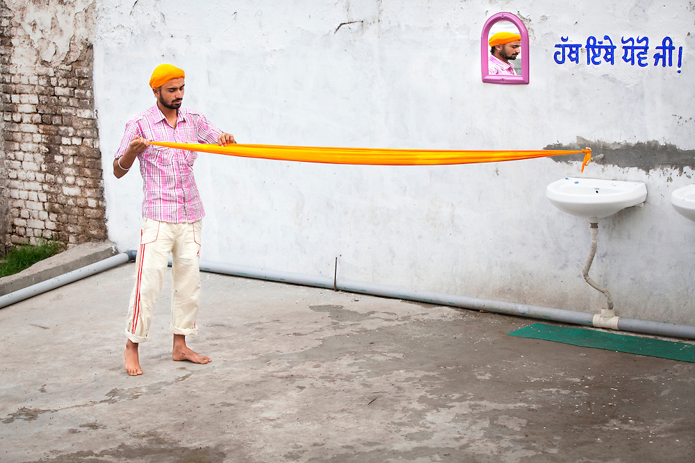 A young Sikh puts on his turban outside of a Sikh kitchen.