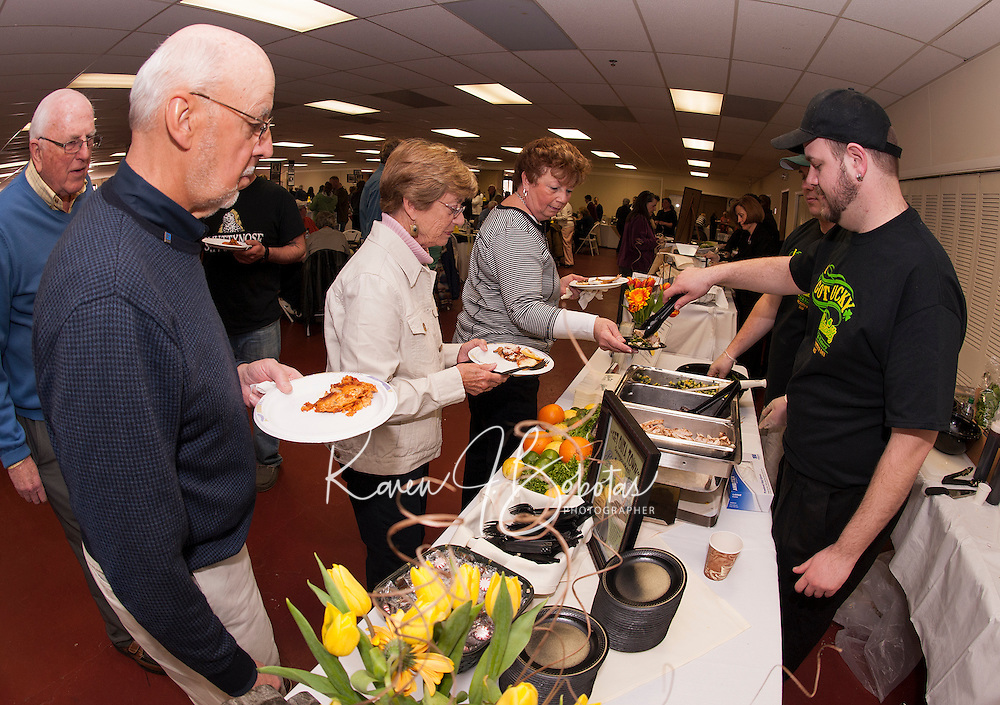 Linda Foster and John Silva wait to try South Sea Salad served by Tracey Sopinsky and Rick Morten of Patrick's Pub and Eatery Sunday afternoon during the annual Altrusa's Taste of the Lakes Region at the Opechee Conference Center.    (Karen Bobotas/for the Laconia Daily Sun)