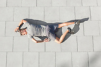 High angle view of tired sporty man lying on tiled sidewalk