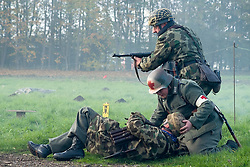 A Re-enactor portrayiing a fallschirmjager gives covering fire as a field medic goes to the aid of a comrade during a battle battle re-enactment in on Pickering Showground<br />
