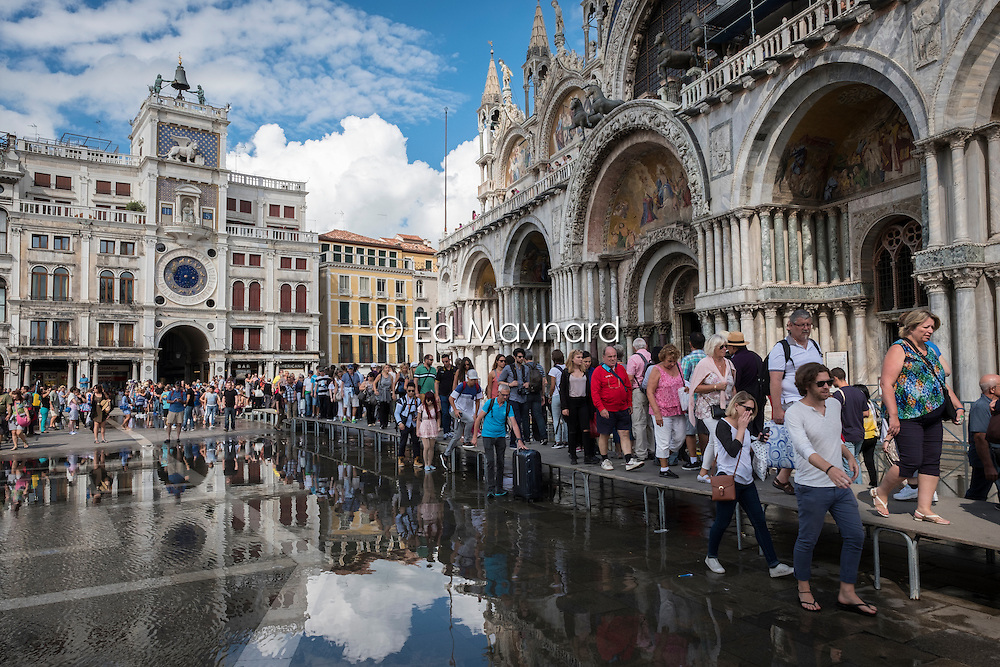 Tourists keep their feet dry and out of the flood water in front of the Basilica di San Marco, Venice, Italy.<br />