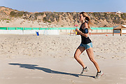 Young woman in her 20's jogs on a beach a music player attached to her arm - model release available