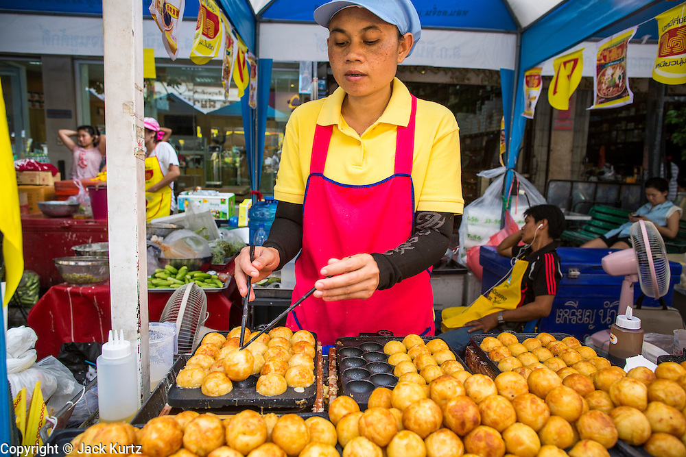 17 OCTOBER 2012 - BANGKOK, THAILAND:    A vegan snack vendor cooks vegan dough balls at the street food fair during the Vegetarian Festival on Yaowarat Road in Bangkok. The Vegetarian Festival is celebrated throughout Thailand. It is the Thai version of the The Nine Emperor Gods Festival, a nine-day Taoist celebration celebrated in the 9th lunar month of the Chinese calendar. For nine days, those who are participating in the festival dress all in white and abstain from eating meat, poultry, seafood, and dairy products. Vendors and proprietors of restaurants indicate that vegetarian food is for sale at their establishments by putting a yellow flag out with Thai characters for meatless written on it in red.         PHOTO BY JACK KURTZ