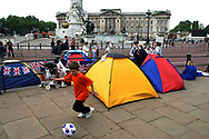 A boy passes the time playing football after he and his family camped out overnight outside Buckingham Palace to secure the best viewing positions for the two-day Golden Jubilee celebrations to mark the 50 year reign of Queen Elizabeth II. Celebrations took place across the United Kingdom with the centrepiece a parade and fireworks at Buckingham Palace, the Queen's London residency. Queen Elizabeth ascended to the British throne in 1952 upon the death of her father, King George VI.
