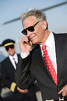Mid-adult businessman talking on phone, airline pilot standing in background.