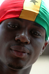 Ghana, Accra, 2007. Clad in a hat made in the pattern of Ghana's flag, a young man poses proudly just off the main road to Independence Square.