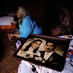 Antonia Gil, 68 - survivor, sits next to her wedding picture.