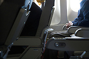elderly passenger sitting comfortable in a airplane with an empty second seat