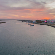 Sunset aerial panoramic seascape view of Olhao dockyard, waterfront to Ria Formosa natural park and Armona island. Algarve. Portugal.