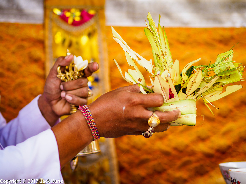 "08 AUGUST 2017 - UBUD, BALI, INDONESIA: A Hindu priest blesses a small basket of offerings during a ceremony to honor a family temple in Ubud, Bali. Balinese Hindus have a 210 day calender and every almost every family compound on Bali has a family temple. Once a year (or every 210 days) families celebrate the ""birthday"" of their temple with a ceremony.     PHOTO BY JACK KURTZ"