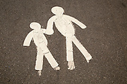 Child and parent  figures holding hands on tarmac pavement, Mumbles, South Wales, UK