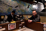 "Yushin whale meat shop proprieter Koji Shingu (left), Asakusa, Tokyo. Next door is his whale meat restaurant, also called Yushin. The meat for both premises comes from the factory vessel Nisshin Maru, which carries out controversial ""scientific whaling research"" in the Southern Ocean every year, killing hundreds of whales in the Southern Ocean Whale Sanctuary. After the whaling fleet arrive back in Japan, the whale meat is sold off to shops like Yushin. Critics, such as Greenpeace, say that the scientific research programme is really just commercial whaling in disguise."