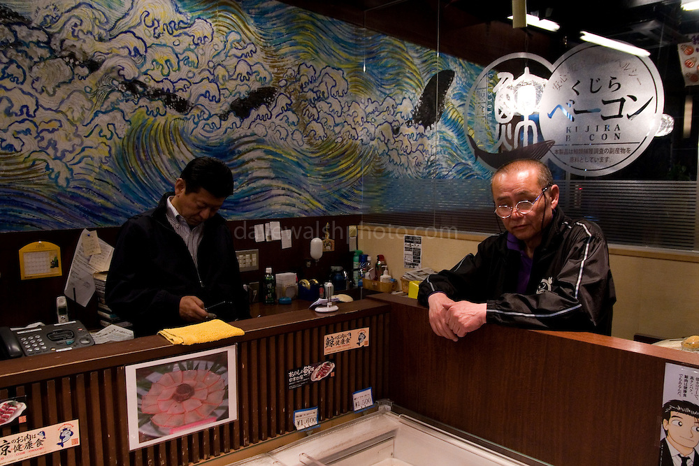 """Yushin whale meat shop proprieter Koji Shingu (left), Asakusa, Tokyo. Next door is his whale meat restaurant, also called Yushin. The meat for both premises comes from the factory vessel Nisshin Maru, which carries out controversial """"scientific whaling research"""" in the Southern Ocean every year, killing hundreds of whales in the Southern Ocean Whale Sanctuary. After the whaling fleet arrive back in Japan, the whale meat is sold off to shops like Yushin. Critics, such as Greenpeace, say that the scientific research programme is really just commercial whaling in disguise."""