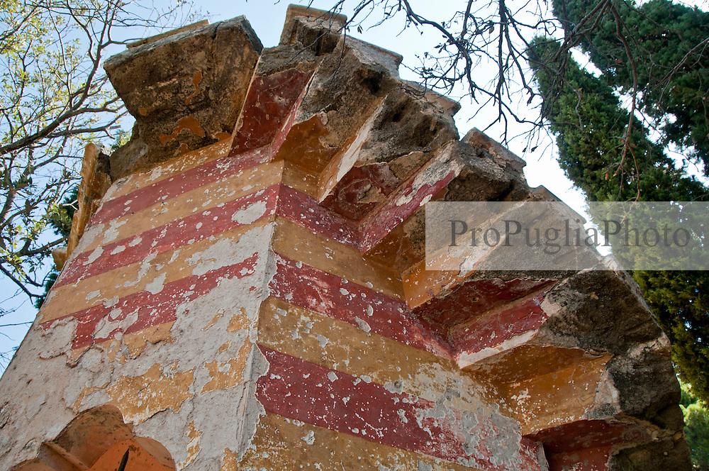 """Particolare di un muro di Villa Tafuri - Reportage fotografico di Alessandro Caniglia, Alessandro De Matteis e Dario Luceri - Il Parco Naturale Regionale di Porto Selvaggio è situato lungo la costa ionica e ricade nel comune di Nardò (Lecce). Definito come """"area di notevole interesse pubblico"""" già nel 1939, è stato effettivamente istituito come Parco nel 2004. I suoi limiti sono compresi tra la baia di Frascone (a nord) e la Torre dell'Alto (a sud). Ha una estensione complessiva di circa 1000 ettari.Porto Selvaggio è una delle zone tra le più incontaminate del litorale Ionico, con un paesaggio caratterizzato da una pineta di ca. 300 ettari e da una macchia mediterranea ricca di acacee e ginestre..Lungo la costa sono presenti molte cavità carsiche, con varie insenature, grotte sommerse.Per gli amanti della natura il paesaggio è estremamente suggestivo in ogni stagione: molto silenzioso e rilassante in autunno, inverno e primavera, ricco di colori e festoso in estate, con il canto delle cicale che accompagna i visitatori lungo i sentieri e di tratti di scogliera che portano fino alla spiaggia. Il mare limpido e azzurro, con un fondale ricco di flora e fauna marina, è spesso meta di numerosi subacquei."""