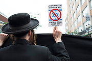 An orthodox Jewish Neturai Karta walking down the street holding a sign denouncing Israeli policy towards Palestinians.