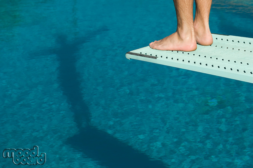 Male swimmer standing on diving board