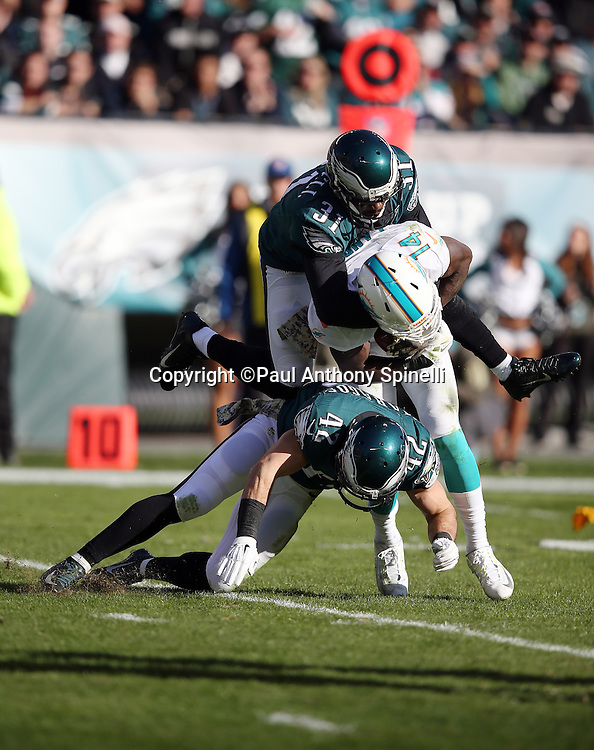 Miami Dolphins wide receiver Jarvis Landry (14) catches a pass and gets gang tackled by Philadelphia Eagles cornerback Byron Maxwell (31) and Philadelphia Eagles free safety Chris Maragos (42) during the 2015 week 10 regular season NFL football game against the Philadelphia Eagles on Sunday, Nov. 15, 2015 in Philadelphia. The Dolphins won the game 20-19. (©Paul Anthony Spinelli)
