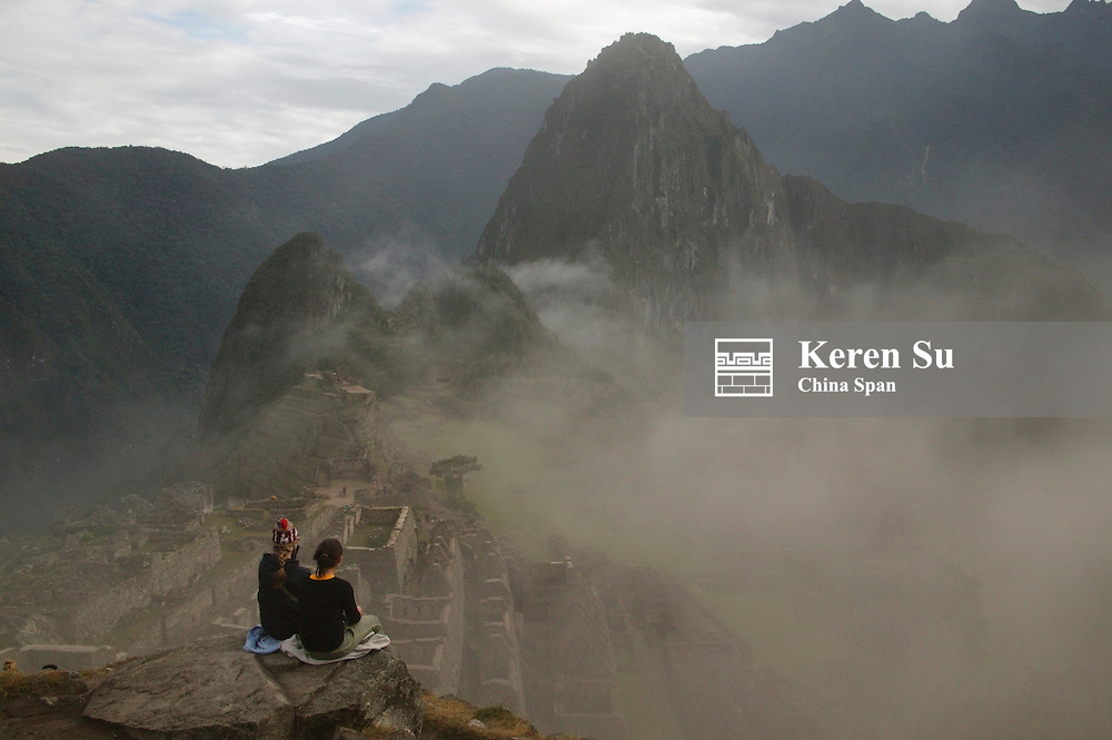 Western travelers at ancient ruins of Machu Picchu in mist with Andes Mountain, Peru (MR)