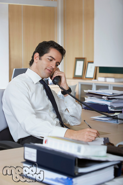 Hispanic businessman using telephone at office desk surrounded by folders