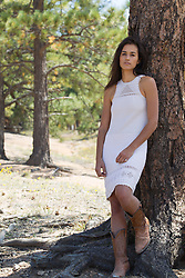 sexy girl in a dress leaning against a large tree in New Mexico