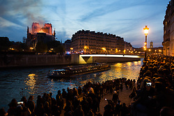Bystanders look on as flames and smoke are seen billowing from the roof at Notre-Dame Cathedral with the Seine and boats by sun set river in Paris on April 15, 2019. A fire broke out at the landmark Notre-Dame Cathedral in central Paris, potentially involving renovation works being carried out at the site, the fire service said.Images posted on social media showed flames and huge clouds of smoke billowing above the roof of the gothic cathedral, the most visited historic monument in Europe. Photo by Raphael Lafargue/ABACAPRESS.COM