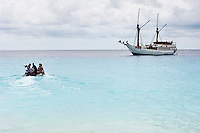 Tourists returning to a Pinisi style liveaboard boat moored off a remote island, Rurbas, West Papua, Indonesia.