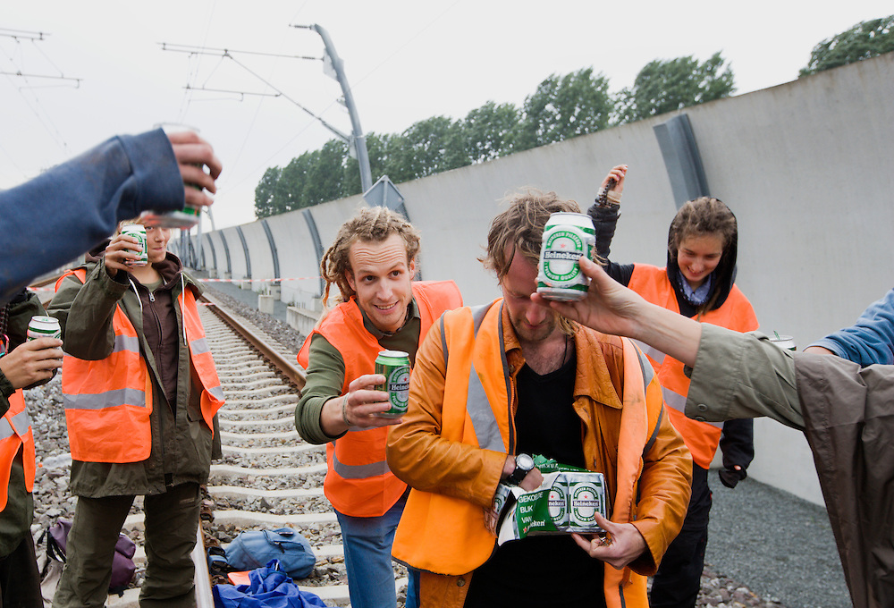 Nederland. Zetten, 16 juni 2007.<br /> Na afloop proosten de actievoerders met een blikje bier op de goede afloop.<br /> Enkele tientallen actievoerders van GroenFront hebben op verschillende plekken op de Betuweroute de spoorbaan geblokkeerd. Op de dag van de offici&euml;le opening van de omstreden goederenlijn ketenden zij zich als laatste symbolisch protest vast aan de rails.<br /> Foto Martijn Beekman <br /> NIET VOOR TROUW, AD, TELEGRAAF, NRC EN HET PAROOL
