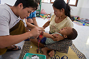 "23 FEBRUARY 2008 -- MAE SOT, TAK, THAILAND: Clinic workers try to start an IV in Ti Su Wa, a 2 year old Karen boy at the Mae Tao Clinic in Mae Sot, Thailand. His mother said he had been sick for more than a week but that she couldn't afford medical care in Burma so she crossed illegally to Thailand to get treatment at the clinic. The clinic treated more than 80,000 people in 2007, all Burmese. Most of them are living illegally in Thailand, but many come to the clinic from Burma because they either can't afford medical care in Burma or because it isn't available to them. There are millions of Burmese refugees living in Thailand. Many live in refugee camps along the Thai-Burma (Myanmar) border, but most live in Thailand as illegal immigrants. They don't have papers and can not live, work or travel in Thailand but they do so ""under the radar"" by either avoiding Thai officials or paying bribes to stay in the country. Most have fled political persecution in Burma but many are simply in search of a better life and greater economic opportunity.  Photo by Jack Kurtz"